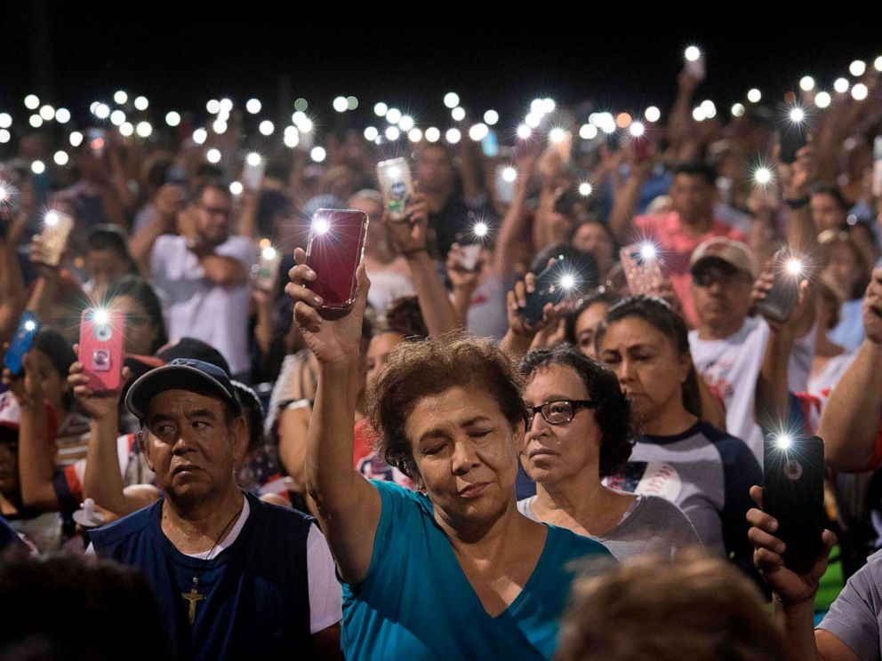 PHOTO: People hold up their phones during a prayer and candle vigil organized by the city, after a shooting at the Cielo Vista Mall Wal-Mart in El Paso, Texas, Aug. 4, 2019.