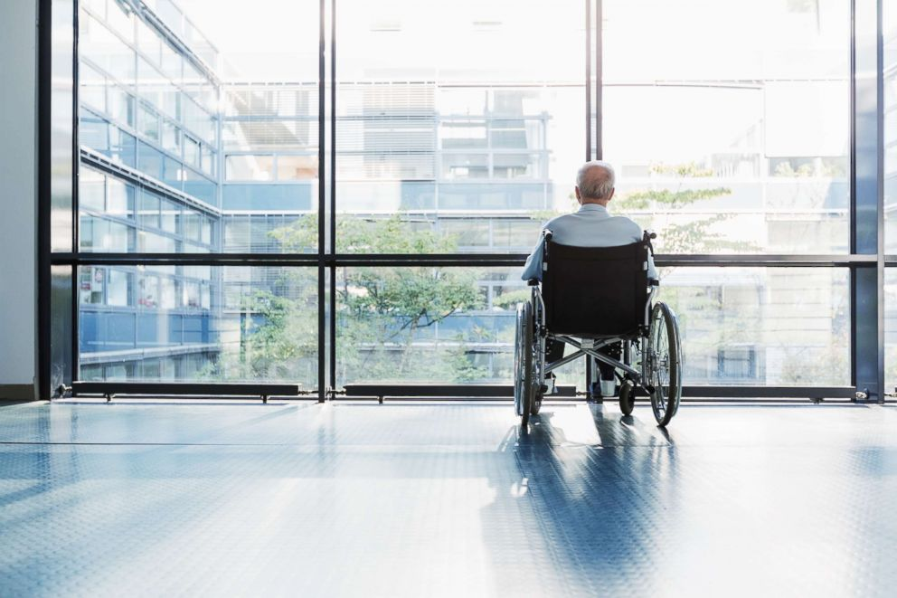 PHOTO: A senior man in a wheelchair looking out of a window in a hospital corridor appears in this undated stock photo.
