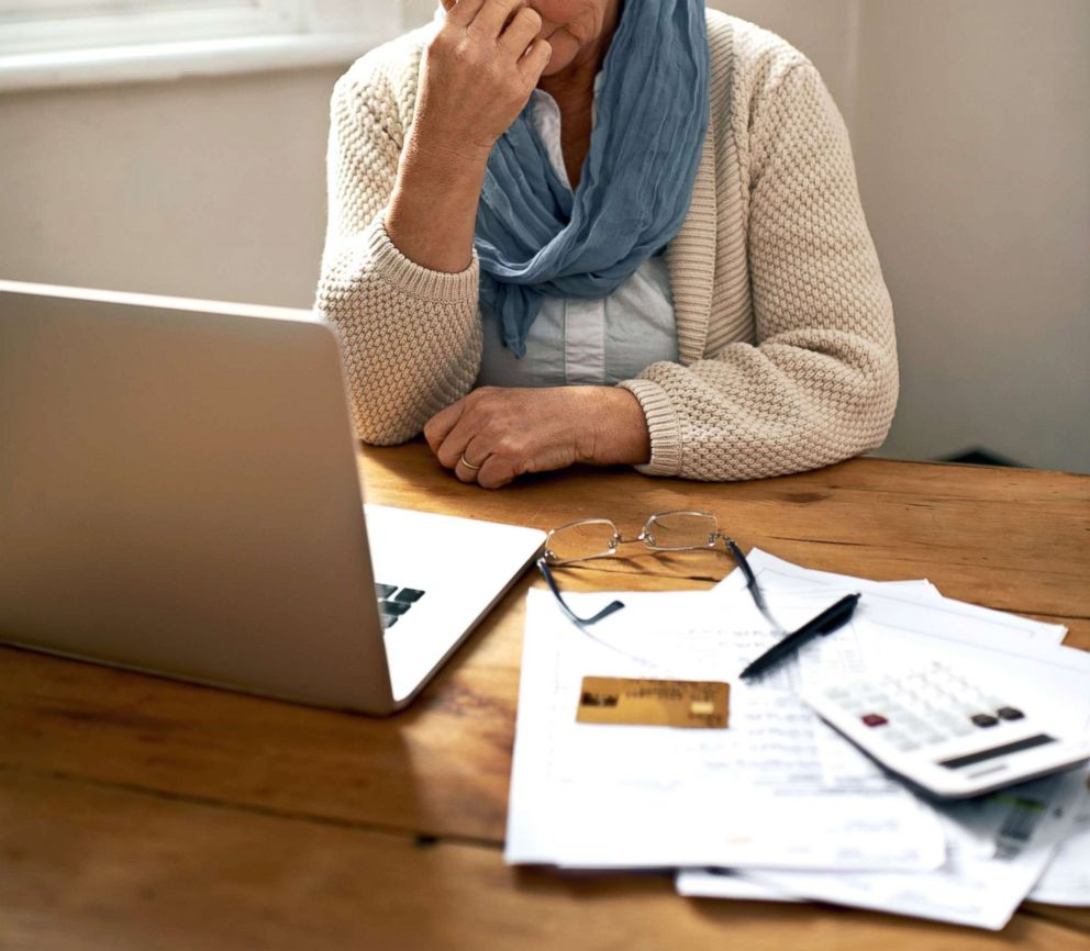 A senior woman sitting in front of a laptop and bills appears in this undated stock photo.