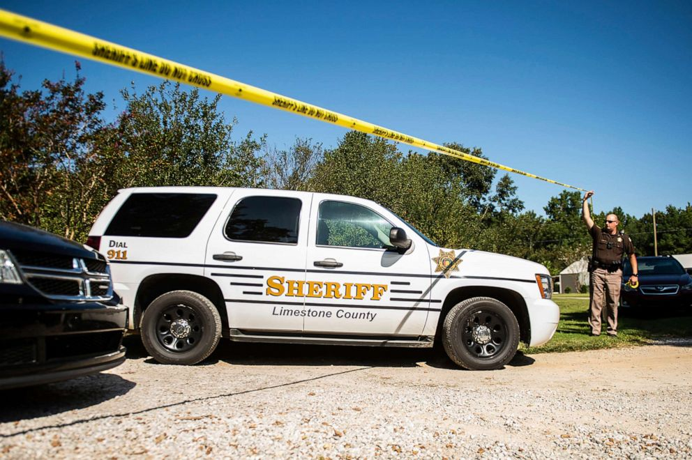 PHOTO: Sgt. Jonathan Hardiman, right, moves caution tape as a Limestone County Sheriff vehicle leaves the scene of a shooting, Sep. 3, 2019, in Elkmont, Ala.