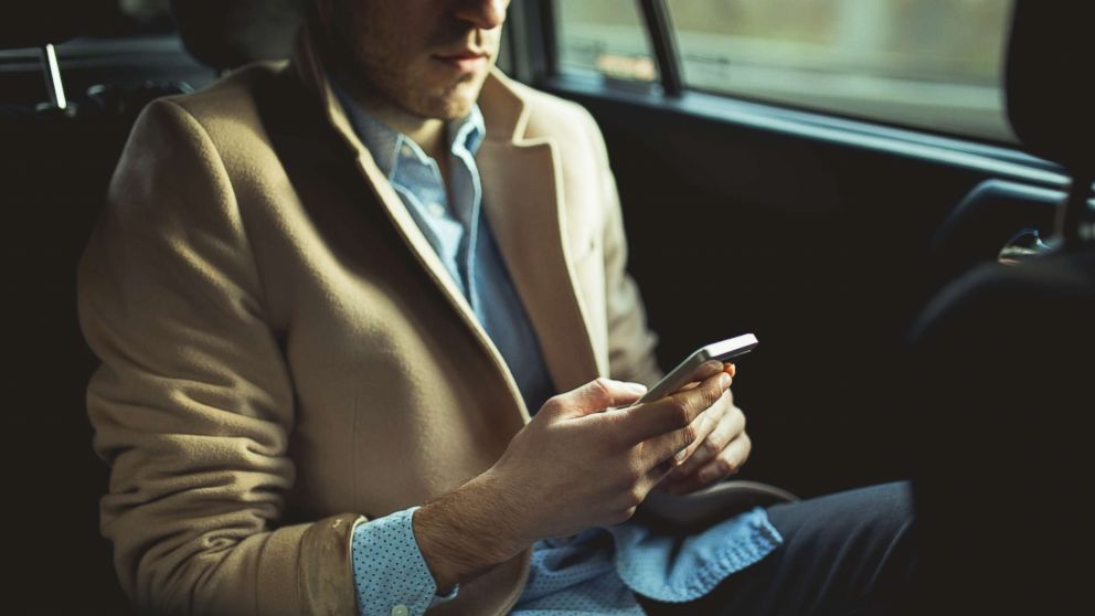 A man using smart phone in the car.