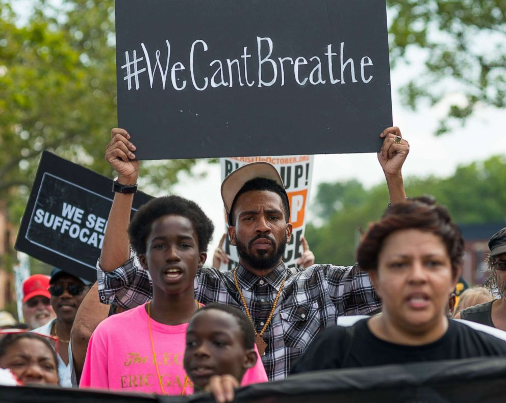 PHOTO: Rally participants hold signs while marching in Staten Island, N.Y., on the second anniversary of the death of Eric Garner, July 17, 2017.
