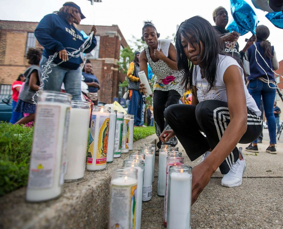 PHOTO: Sherika Logan lights candles for her uncle during a vigil for Eric Logan Monday, June 17, 2019 on Washington Street in South Bend, Ind.