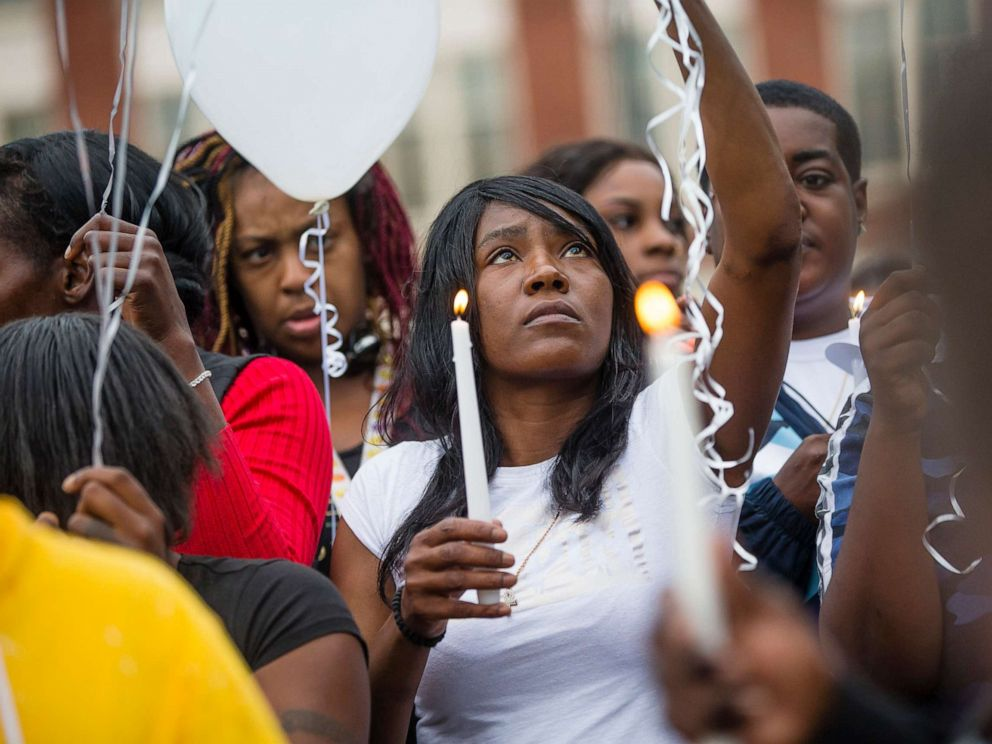 PHOTO: Sherika Logan looks up during a vigil for Eric Logan Monday, June 17, 2019 on Washington Street in South Bend, Ind.