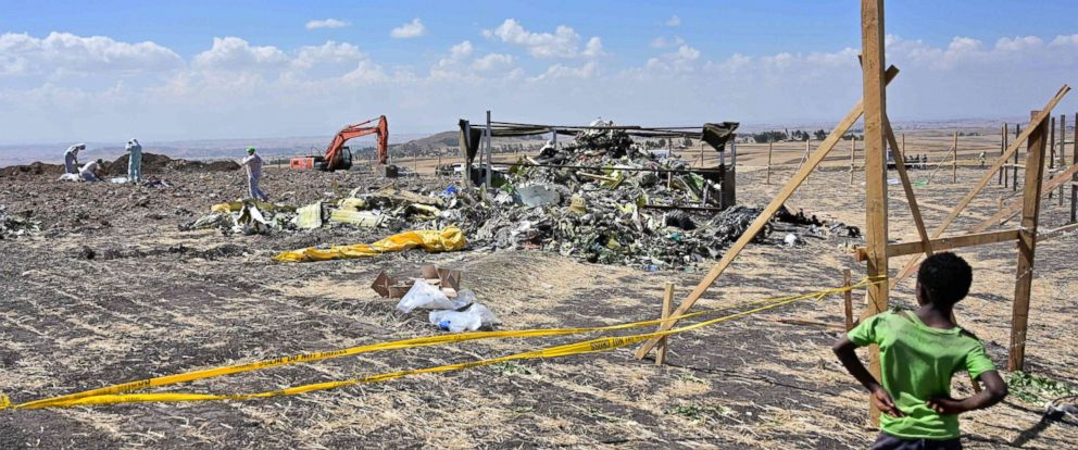 PHOTO: A boy look as forensic investigators comb the ground for DNA evidence near a pile of twisted airplane debris at the crash site of an Ethiopian airways operated Boeing 737 MAX aircraft, March 16, 2019, near Bishoftu in Ethiopia.