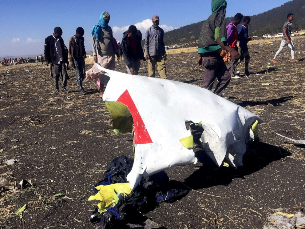 PHOTO: People walk past a part of the wreckage at the scene of the Ethiopian Airlines Flight ET 302 plane crash, near the town of Bishoftu, southeast of Addis Ababa, Ethiopia, March 10, 2019.