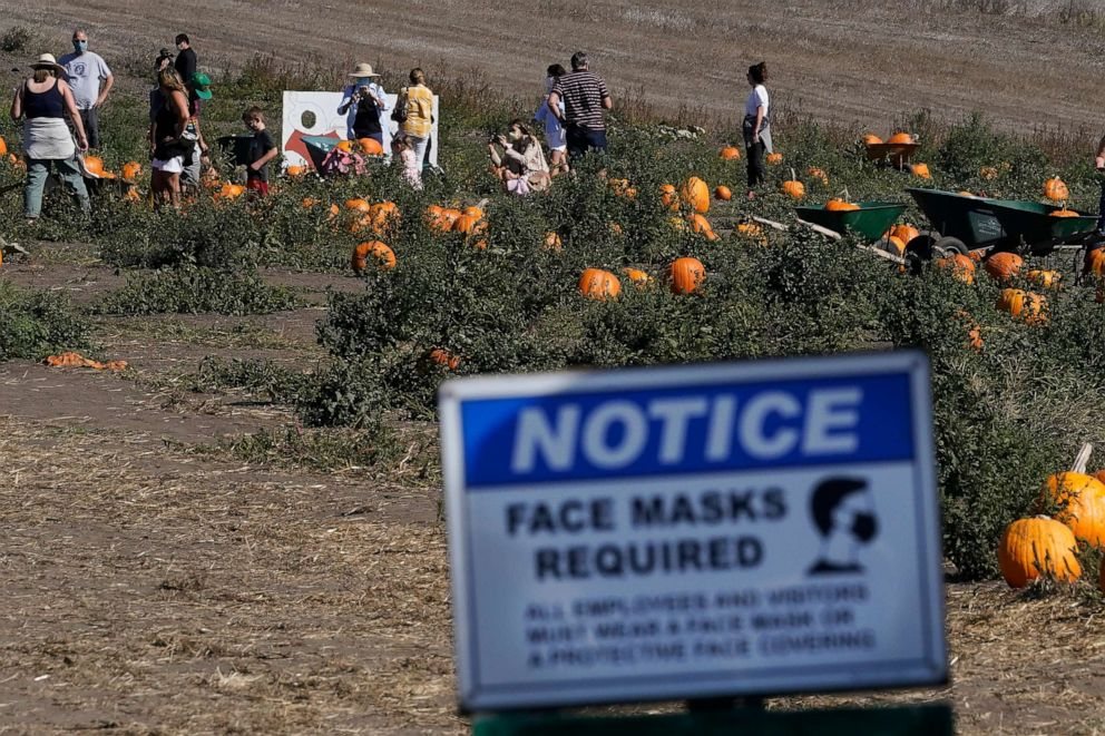 PHOTO: A sign advising face masks being required is posted as people walk inside Bob's Pumpkin Patch in Half Moon Bay, California, on Oct. 12, 2020.
