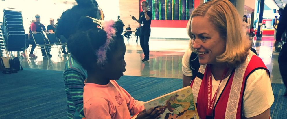 PHOTO: A Red Cross volunteer gives Tabitha Barnes children books to read.