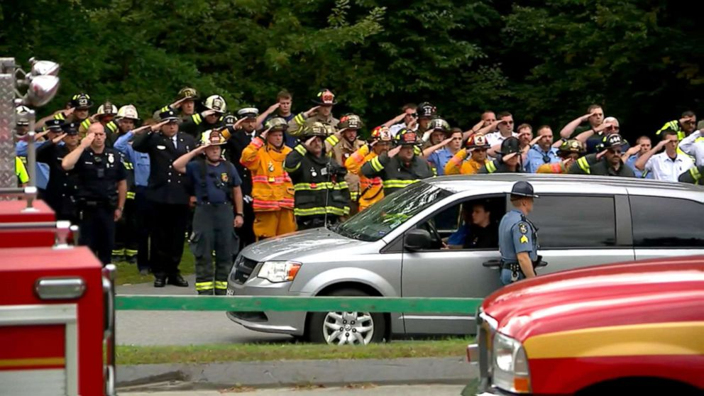 PHOTO: Firefighters salute outside of the Medical Examiners Office after a firefighter was killed in an explosion in Farmington, Maine, Sept. 16, 2019.