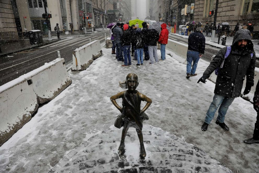 PHOTO: Pedestrians walk past a snow covered Fearless Girl sculpture during a late season noreaster in New York, March 21, 2018.