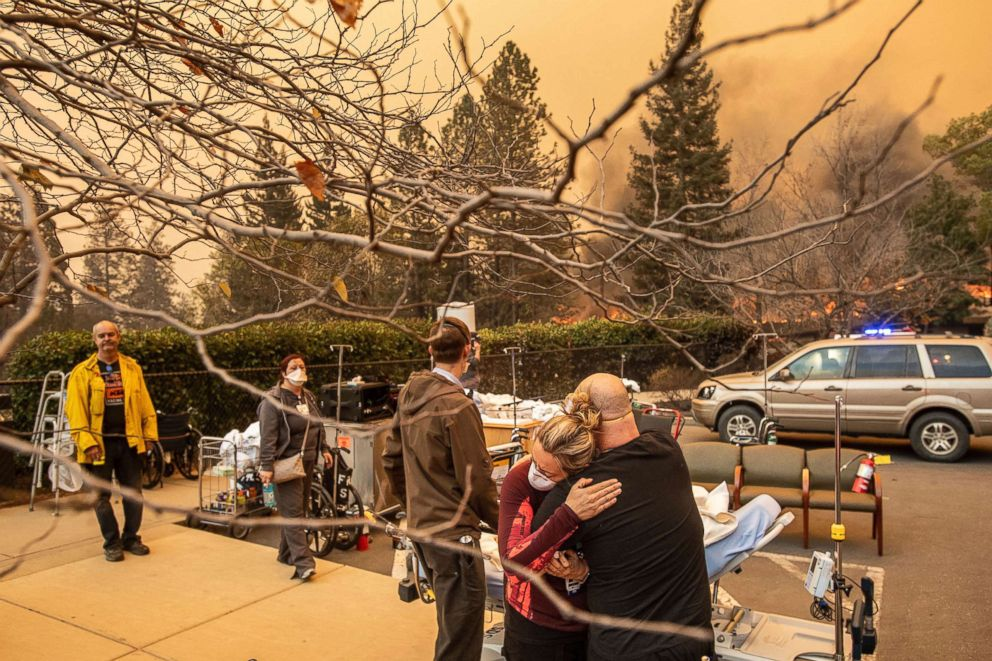 PHOTO: Nurse Cassie Lerossignol hugs as coworker as the Feather River Hospital burns while the Camp Fire rages through Paradise, Calif., Nov. 8, 2018.