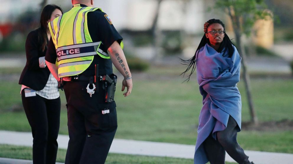 An employee wrapped in a blanket talks to a police officer after she was evacuated at a FedEx distribution center where a package exploded, March 20, 2018, in Schertz, Texas.