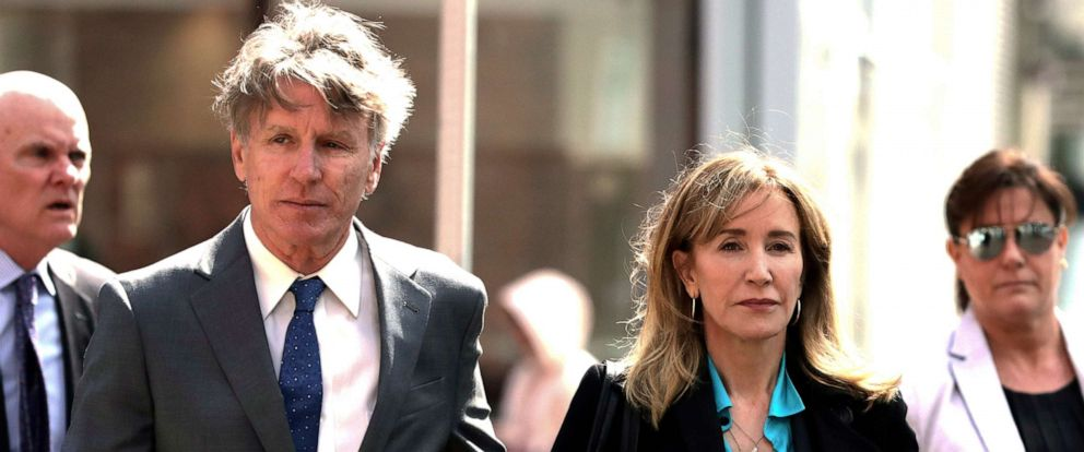 PHOTO: Felicity Huffman arrives holding hands with her brother Moore Huffman Jr., left, at federal court in Boston on Wednesday, April 3, 2019, to face charges in a nationwide college admissions bribery scandal.