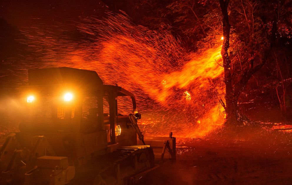 PHOTO: Embers fly off a tree as a bulldozer is prepared to help fight fire during the Kincade fire near Geyserville, California on October 24, 2019.