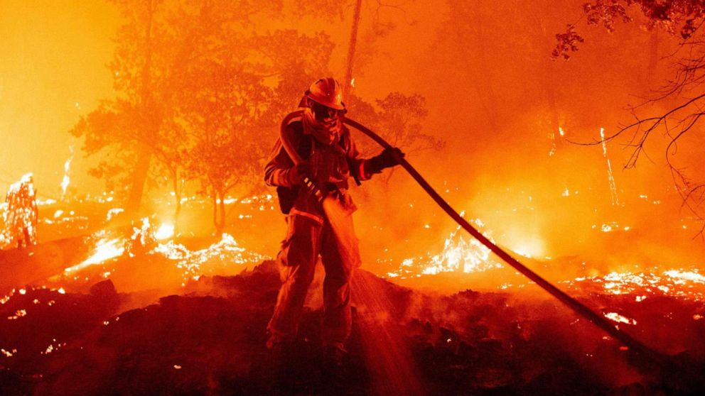 PHOTO: A firefighter douses flames as they push towards homes during the Creek fire in the Cascadel Woods area of unincorporated Madera County, Calif., Sept. 7, 2020.