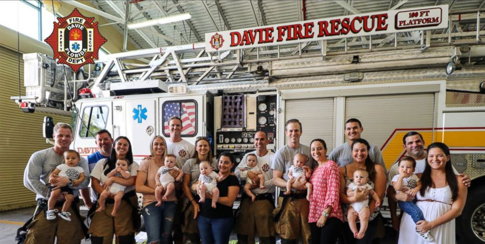 Firefighters in Davie, Fla, pose for a group photo with family members and babies all born in less than a year.