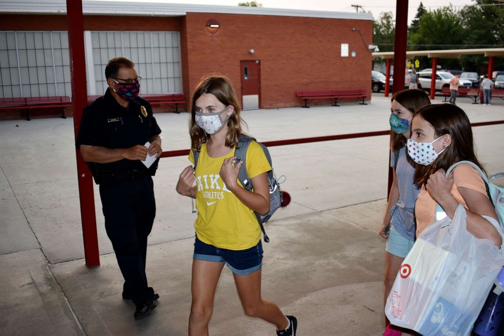 PHOTO: Students wearing masks enter Lewis and Clark Middle School for the first day of classes as a school resource officer looks on in Billings, Montana, on Aug. 24, 2020.