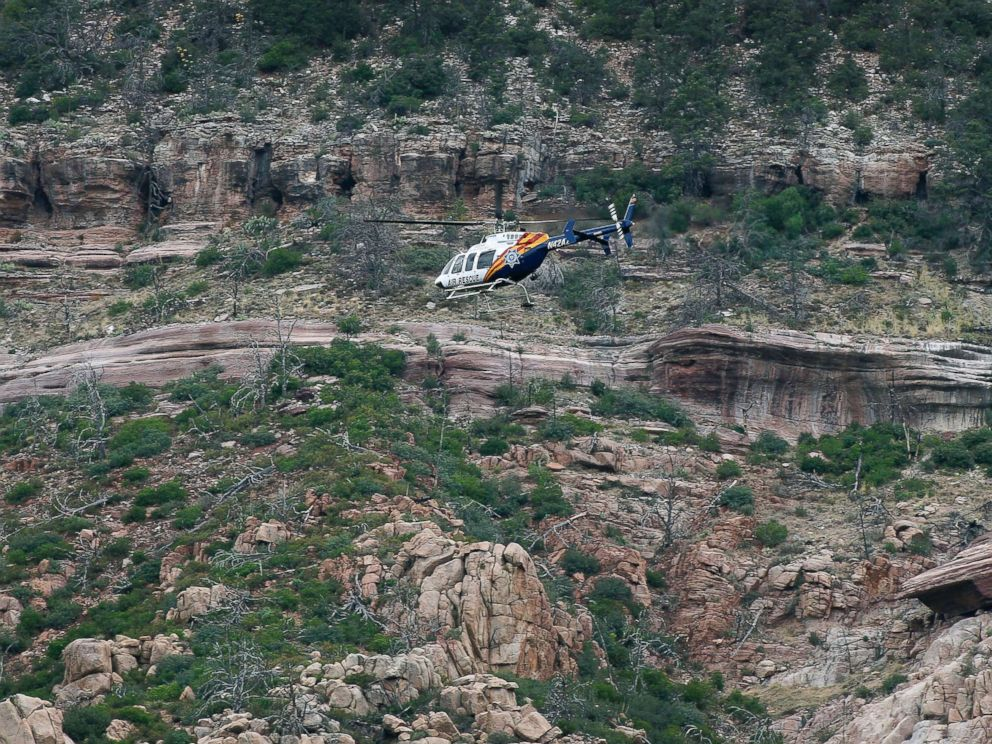 PHOTO: A helicopter flies above the rugged terrain along the banks of the East Verde River during a search and rescue operation for victims of a flash flood, July 16, 2017, in Payson, Ariz.