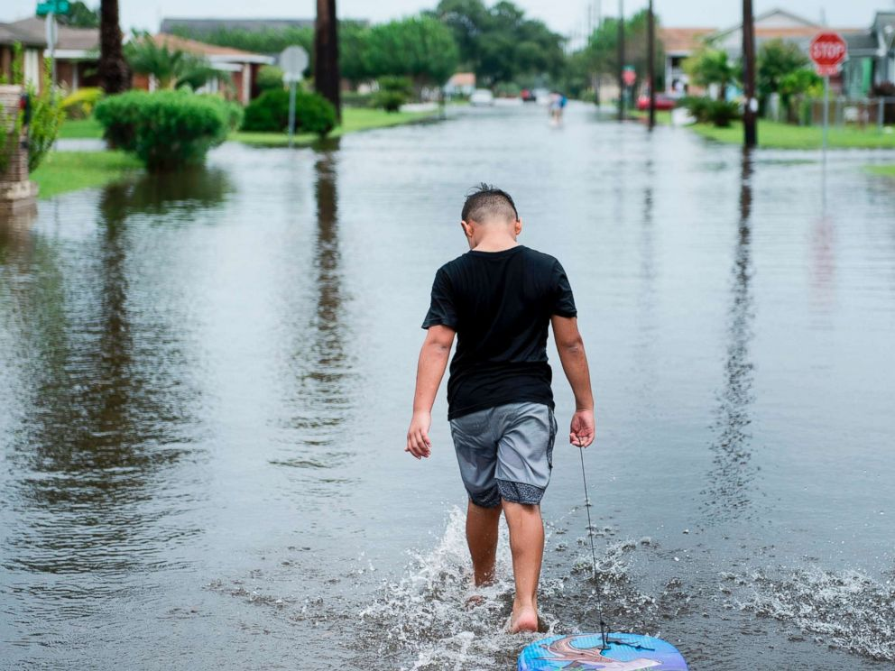PHOTO: A boy walks with a bodyboard through a flooded street as the effects of Hurricane Harvey are seen Aug. 26, 2017 in Galveston, Texas.