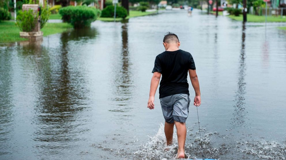A boy walks with a bodyboard through a flooded street as the effects of Hurricane Harvey are seen Aug. 26, 2017 in Galveston, Texas.