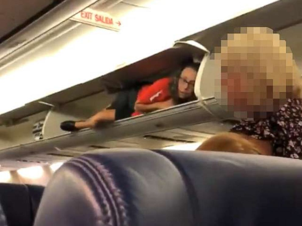 PHOTO: A Southwest Airlines flight attendant was filmed lying inside an overhead bin as passengers boarded a flight from Nashville to Atlanta.