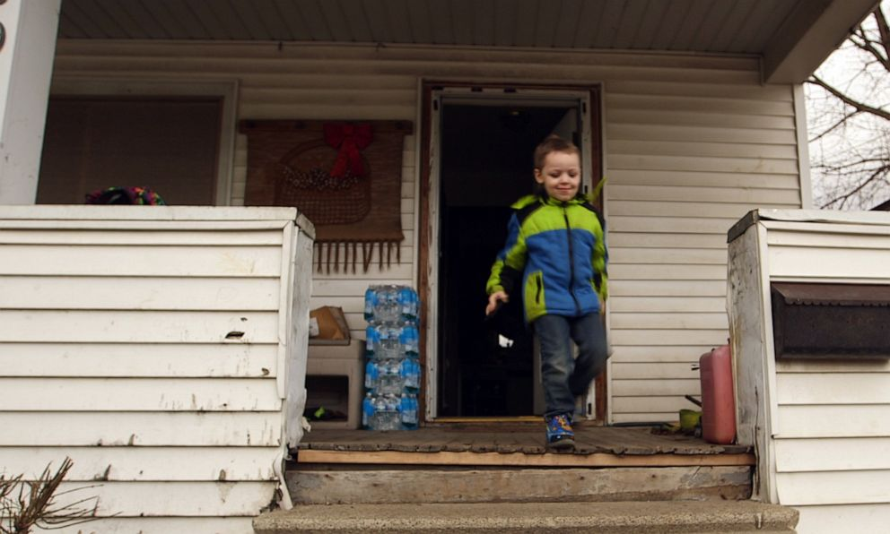 PHOTO: Four-year-old Michael Uherek runs to the car as cases of water bottles collected from a distribution center sit outside his familys home in Flint, Mich.