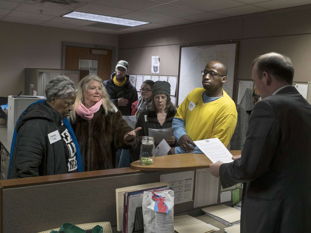 PHOTO: Alongside other protesters, Gladyes Williamson, of Flint, Michigan, delivers a list of demands, including a demand to keep water distribution sites open, to the offices of state representatives on April 11, 2018 in Lansing, Michigan.