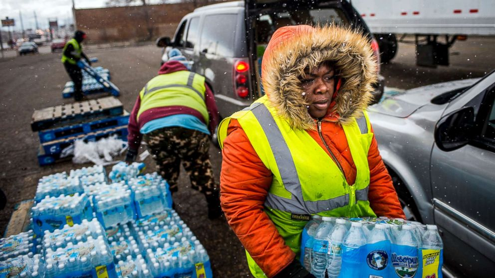 Flint resident Nia Augustine, 26, carries two cases of free bottled water as she fills a vehicle's trunk with eight cases at a water distribution center while cars line up more than 50 deep on Dort Highway, April 6, 2018 in Flint, Mich.