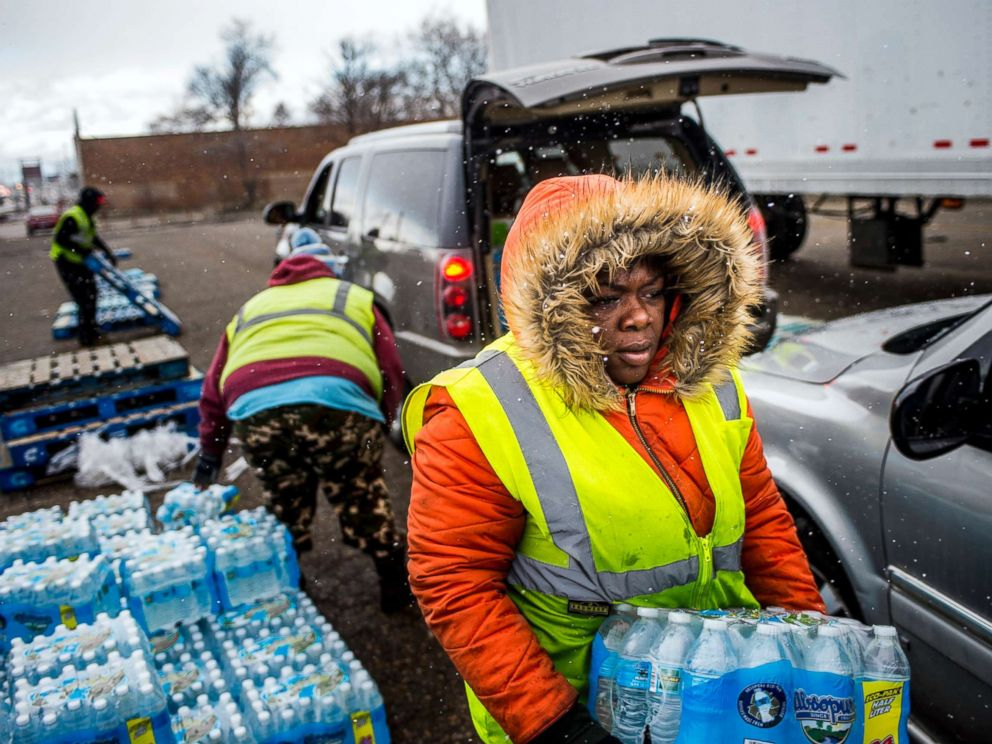 PHOTO: Flint resident Nia Augustine, 26, carries two cases of free bottled water as she fills a vehicles trunk with eight cases at a water distribution center while cars line up more than 50 deep on Dort Highway, April 6, 2018 in Flint, Mich.