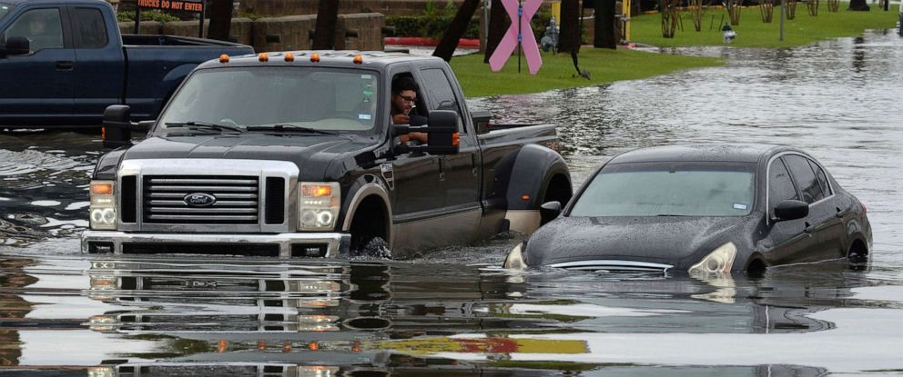 PHOTO: A driver takes a cellphone photo of a flooded car on the Interstate 10 feeder road Thursday, Sept. 19, 2019, in Southeast Texas.