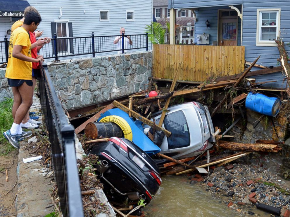 PHOTO: Residents gather by a bridge to look at cars left crumpled in one of the tributaries of the Patapsco River that burst its banks as it channeled through historic Main Street in Ellicott City, Md., May 28, 2018. Missing National Guardsman was trying to rescue woman when swept away in floodwaters: 'He's a hero' Missing National Guardsman was trying to rescue woman when swept away in floodwaters: 'He's a hero' flooding 2 ap er 180529 hpMain 4x3 992