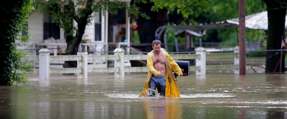 PHOTO: David Dick wades out of the water after checking on his flooded home in Sperry, Okla., Tuesday, May 21, 2019.