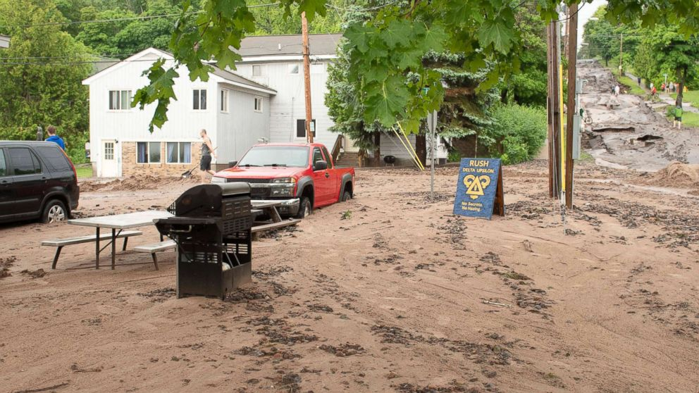In this photo taken June 17, 2018, Agate Street is washed out wth dirt and debris covering the vehicles in Houghton, Mich.