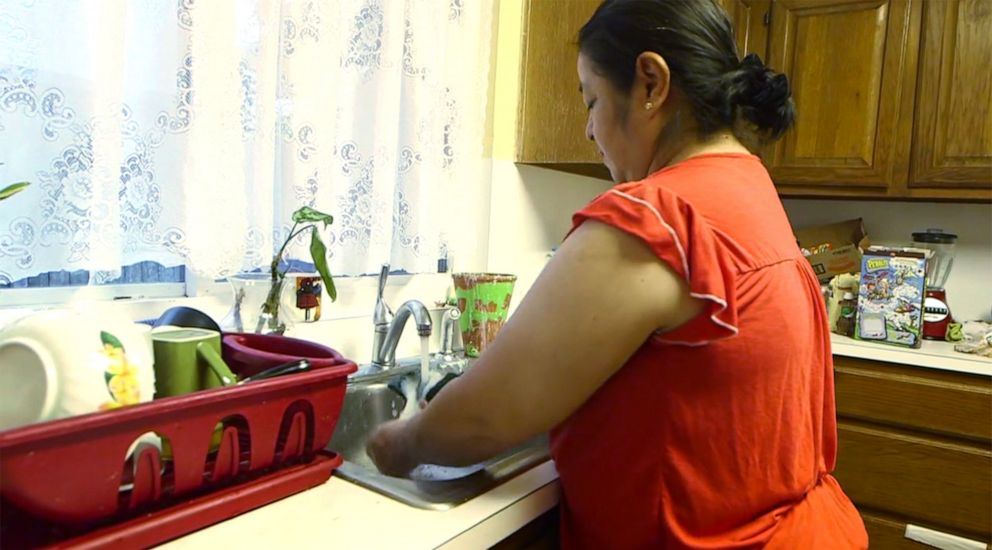 PHOTO: Flor Marquez washes dishes after dinner in her home in Houston, Sept. 10, 2019.