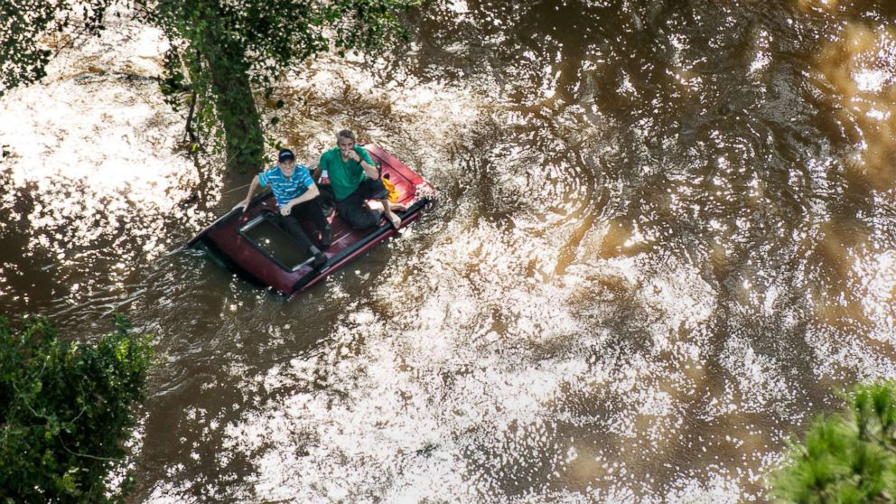 Two people sit on the roof of a vehicle trapped in floodwaters from Hurricane Florence, Sept. 17, 2018 in Wallace, S.C.