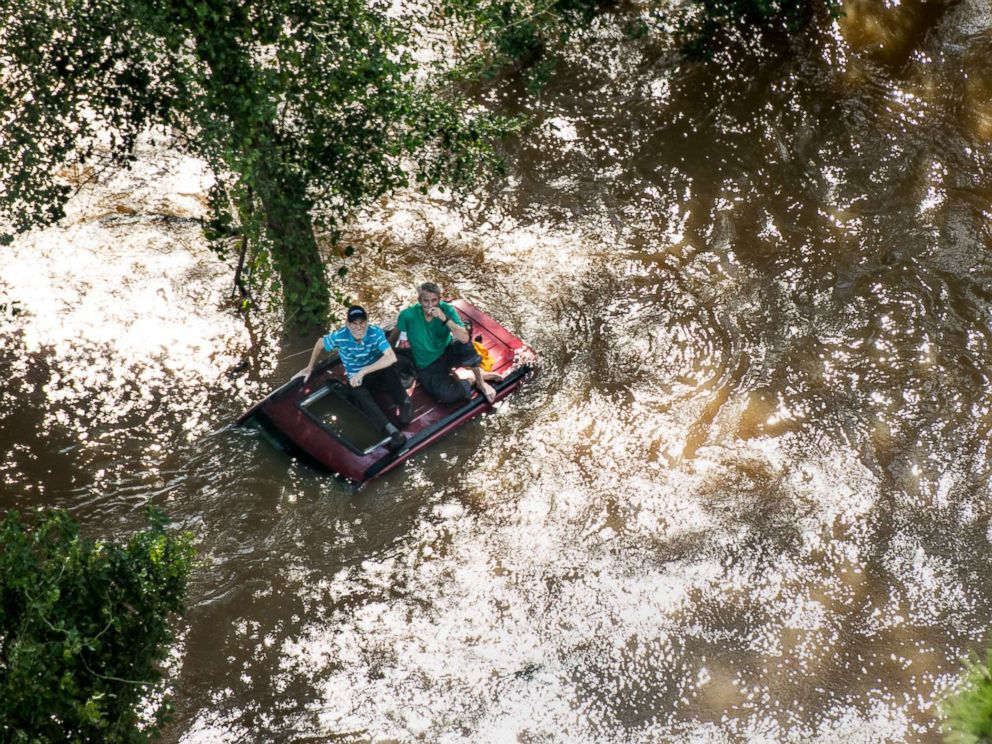 PHOTO: Two people sit on the roof of a vehicle trapped in floodwaters from Hurricane Florence, Sept. 17, 2018 in Wallace, S.C.