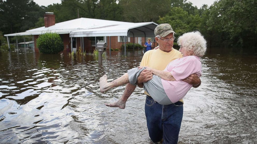 Bob Richling carries Iris Darden as water from the Little River starts to seep into her home, Sept. 17, 2018 in Spring Lake, N.C.
