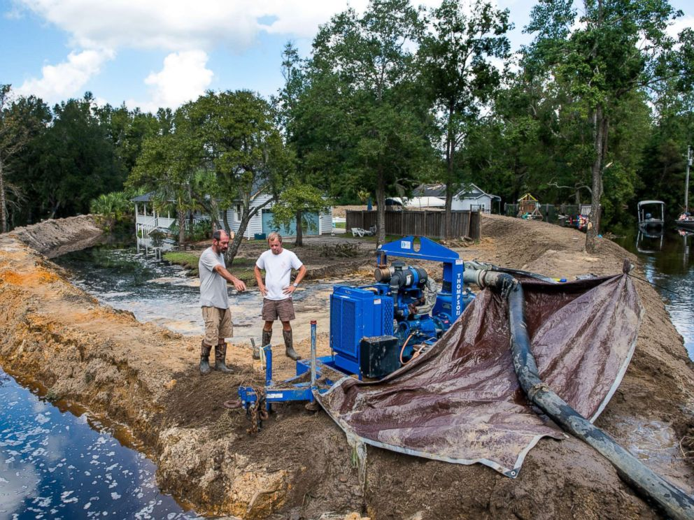 PHOTO: Jason Johnson, left, and homeowner Archie Sanders work to build a temporary levee to hold back floodwaters caused by Hurricane Florence near the Waccamaw River on Sept. 23, 2018 in Conway, S.C.