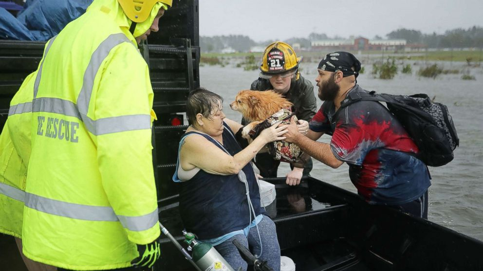 Rescue workers from Township No. 7 Fire Department and volunteers from the Civilian Crisis Response Team help rescue a woman and her dog from their flooded home during Hurricane Florence, Sept. 14, 2018, in James City, N.C.