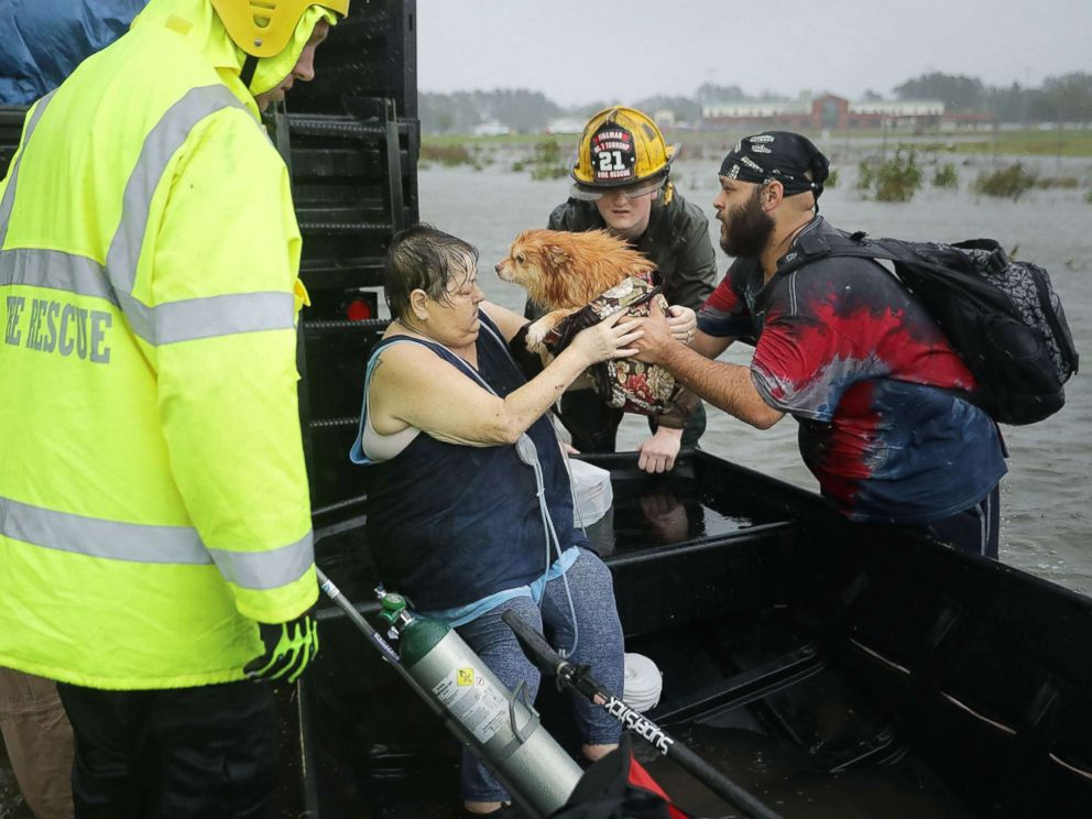 PHOTO: Rescue workers from Township No. 7 Fire Department and volunteers from the Civilian Crisis Response Team help rescue a woman and her dog from their flooded home during Hurricane Florence, Sept. 14, 2018, in James City, N.C.