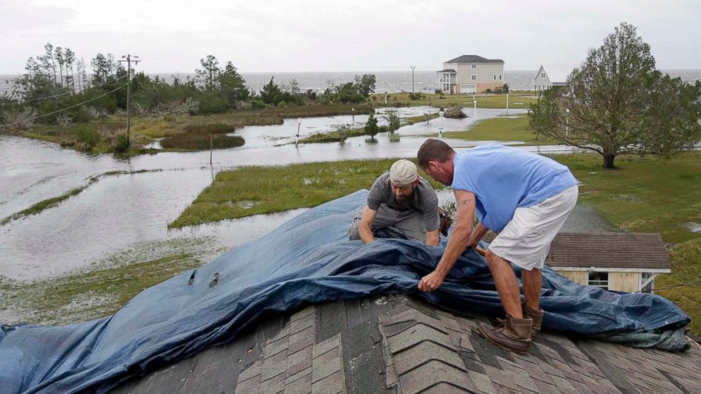 """Jeff Pyron, left, and Daniel Lilly cover Lilly's roof after Hurricane Florence hit Davis N.C., Saturday, Sept. 15, 2018. The town had 4 1/2 feet of storm surge. """"I had my house raised for Irene cause I got flooded from the bottom, now i'm getting flooded from the top,"""" Lilly said."""