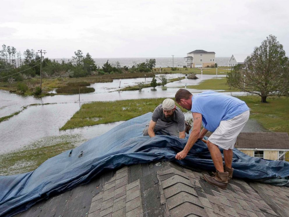 Jeff Pyron, left, and Daniel Lilly cover Lillys roof after Hurricane Florence hit Davis N.C., Saturday, Sept. 15, 2018. The town had 4 1/2 feet of storm surge.