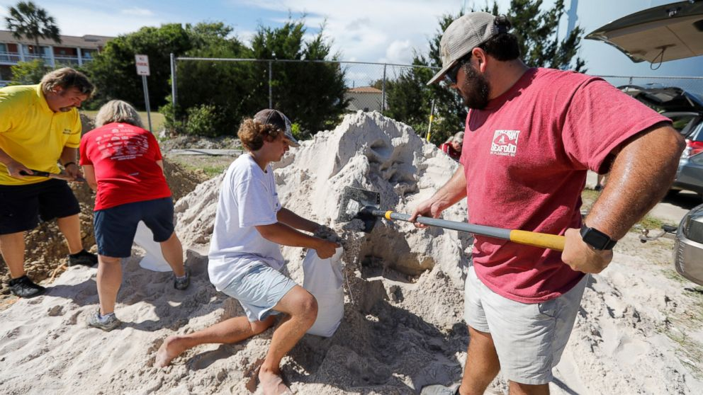Walker Townsend, at right, from the Isle of Palms, S.C., fills a sand bag while Dalton Trout, in center, holds the bag at the Isle of Palms municipal lot where the city was giving away free sand in preparation for Hurricane Florence at the Isle of Palms S.C., Monday, Sept. 10, 2018.
