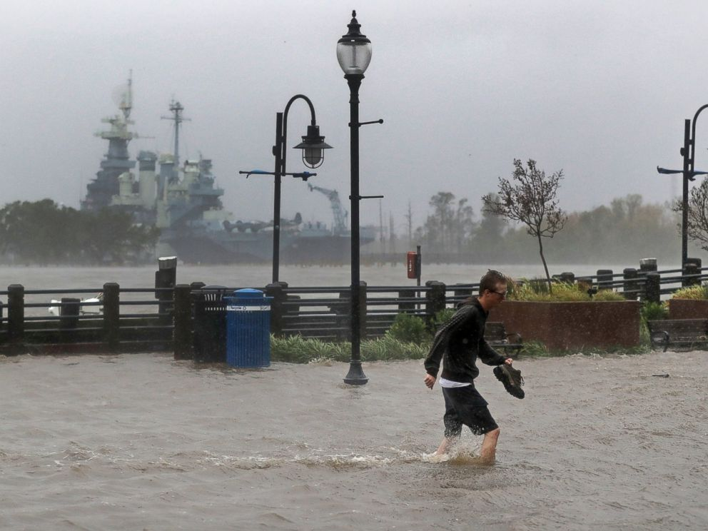 APA man crosses a flooded street in downtown Wilmington N.C. after Hurricane Florence made landfall Friday Sept. 14 2018