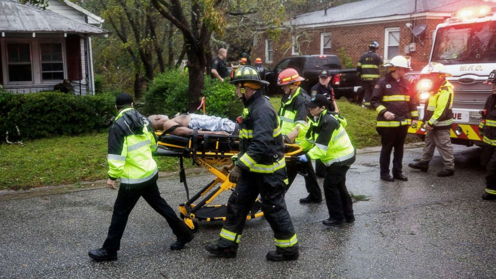Rescue workers rush a man to an ambulance after a giant tree fell on a house in Wilmington, N.C. as Hurricane Florence came ashore, Sept. 14, 2018. A mother and infant were killed in the incident, the father was transported with injuries.