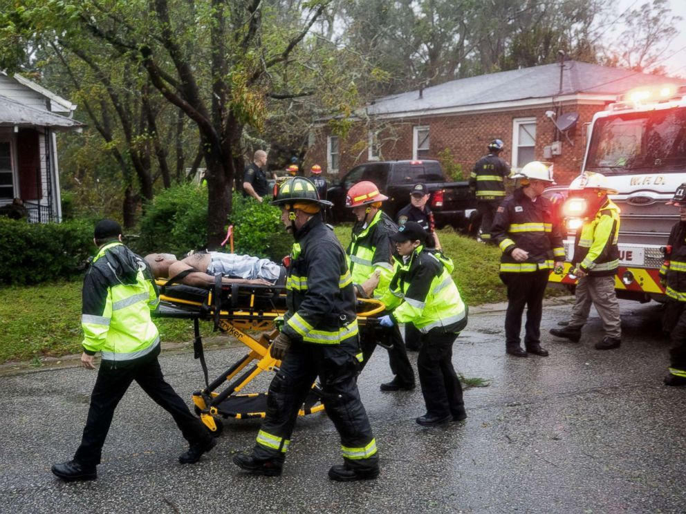 PHOTO: Rescue workers rush a man to an ambulance after a giant tree fell on a house in Wilmington, N.C. as Hurricane Florence came ashore, Sept. 14, 2018.