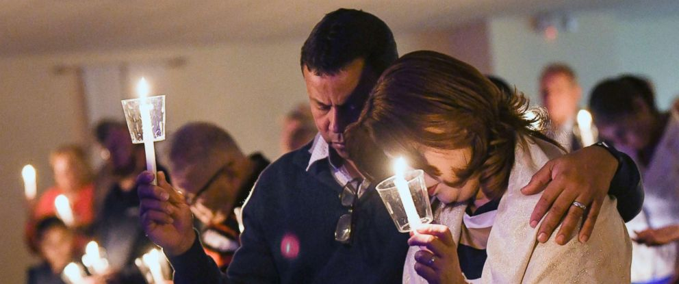 PHOTO: Orlando Vellon and his wife Angie hold candles at Nuevo Pacto United Methodist Church in Sebring during a memorial service in memory of Marisol Lopez and the other victims of a shooting at SunTrust Bank, Jan. 24, 2019.