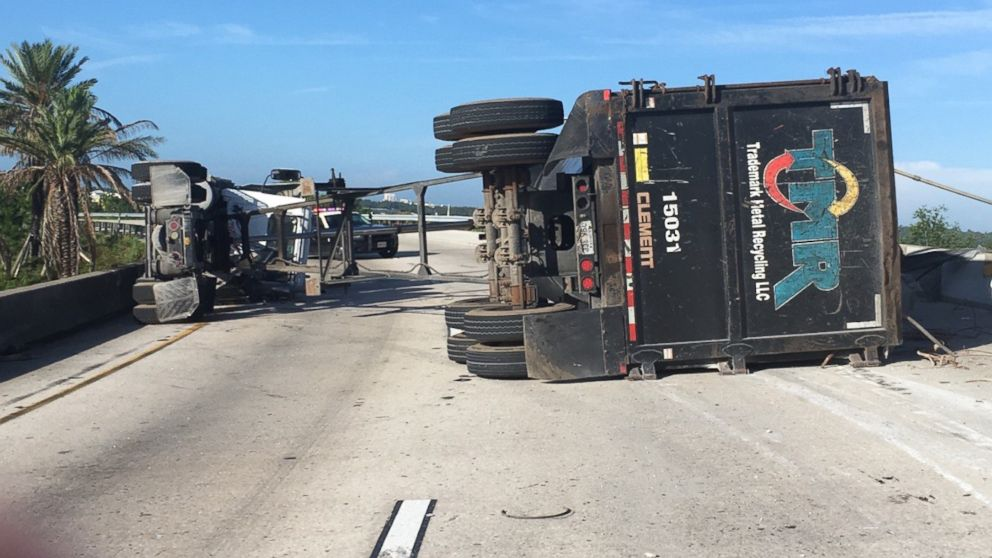 A man survived after a large piece of scrap metal fell from a truck that lost control and overturned on a highway, crushing his vehicle under the overpass, Orange County, Fla., July 15, 2017.
