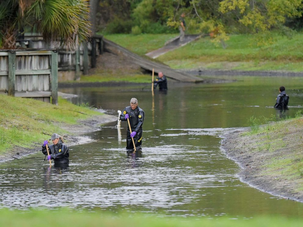 PHOTO: Law enforcement investigators in dry suits search the small retention pond near the entrance of the Southside Villas apartment complex in Jacksonville, Fla., Nov. 6, 2019.