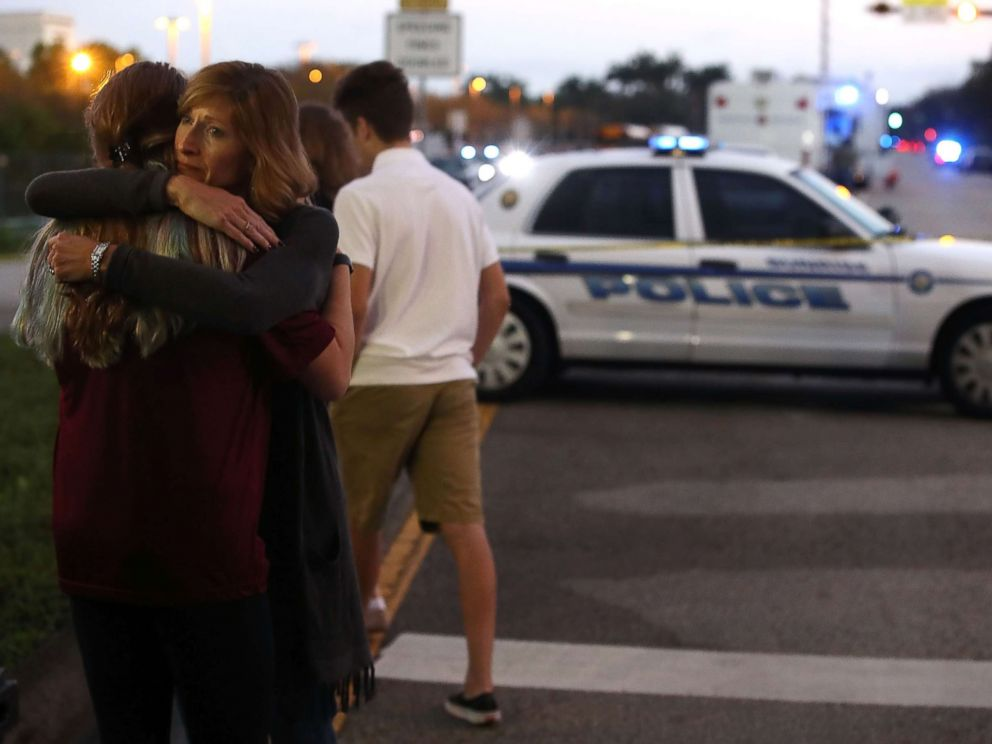 PHOTO: Kristi Gilroy hugs a young woman at a police check point, Feb. 15, 2018, near the Marjory Stoneman Douglas High School where 17 people yesterday were killed by a gunman in Parkland, Fla.